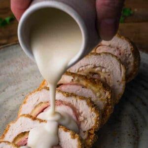 Pouring creamy parmesan sauce over chicken cordon bleu