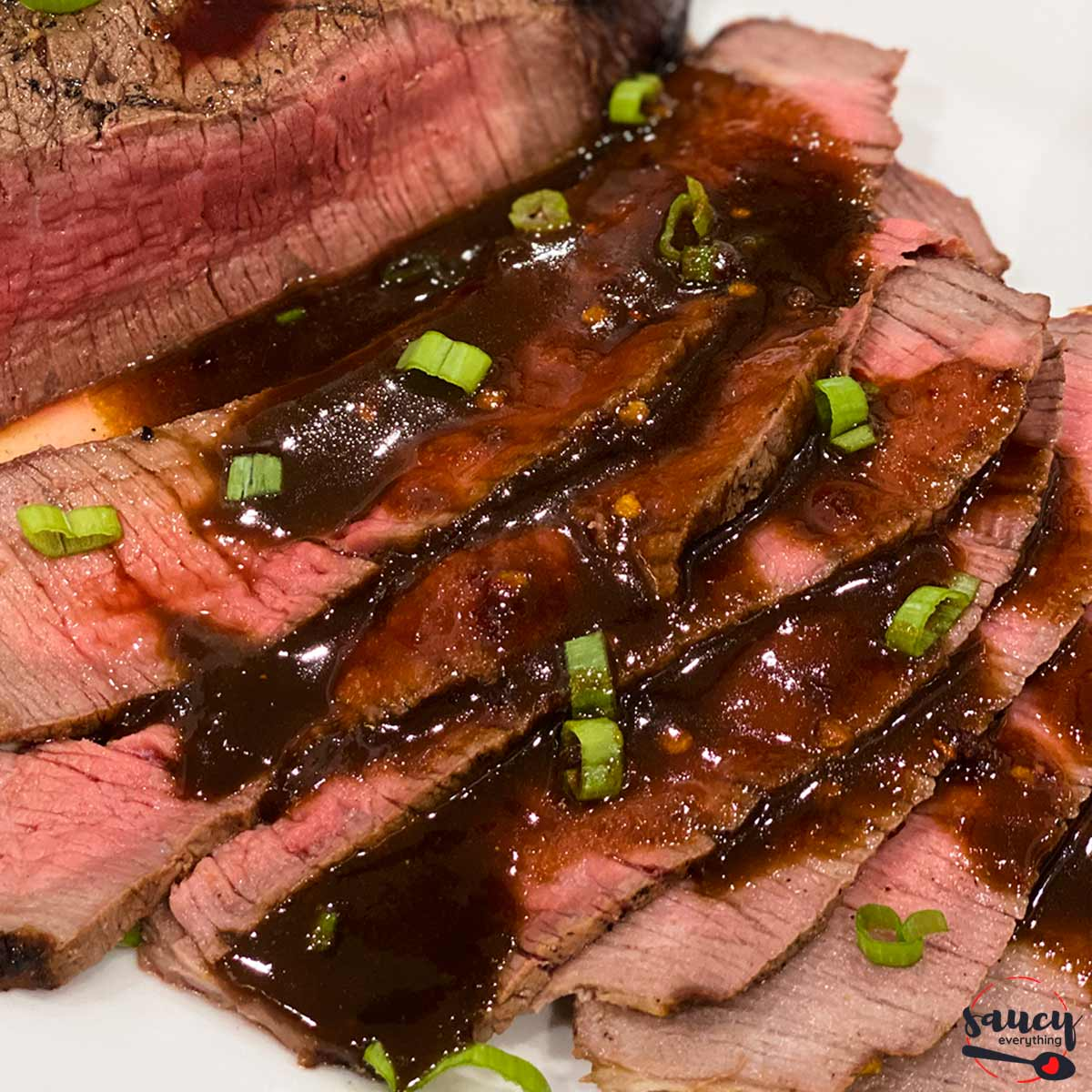 Slices of grilled london broil covered in sauce and green onions