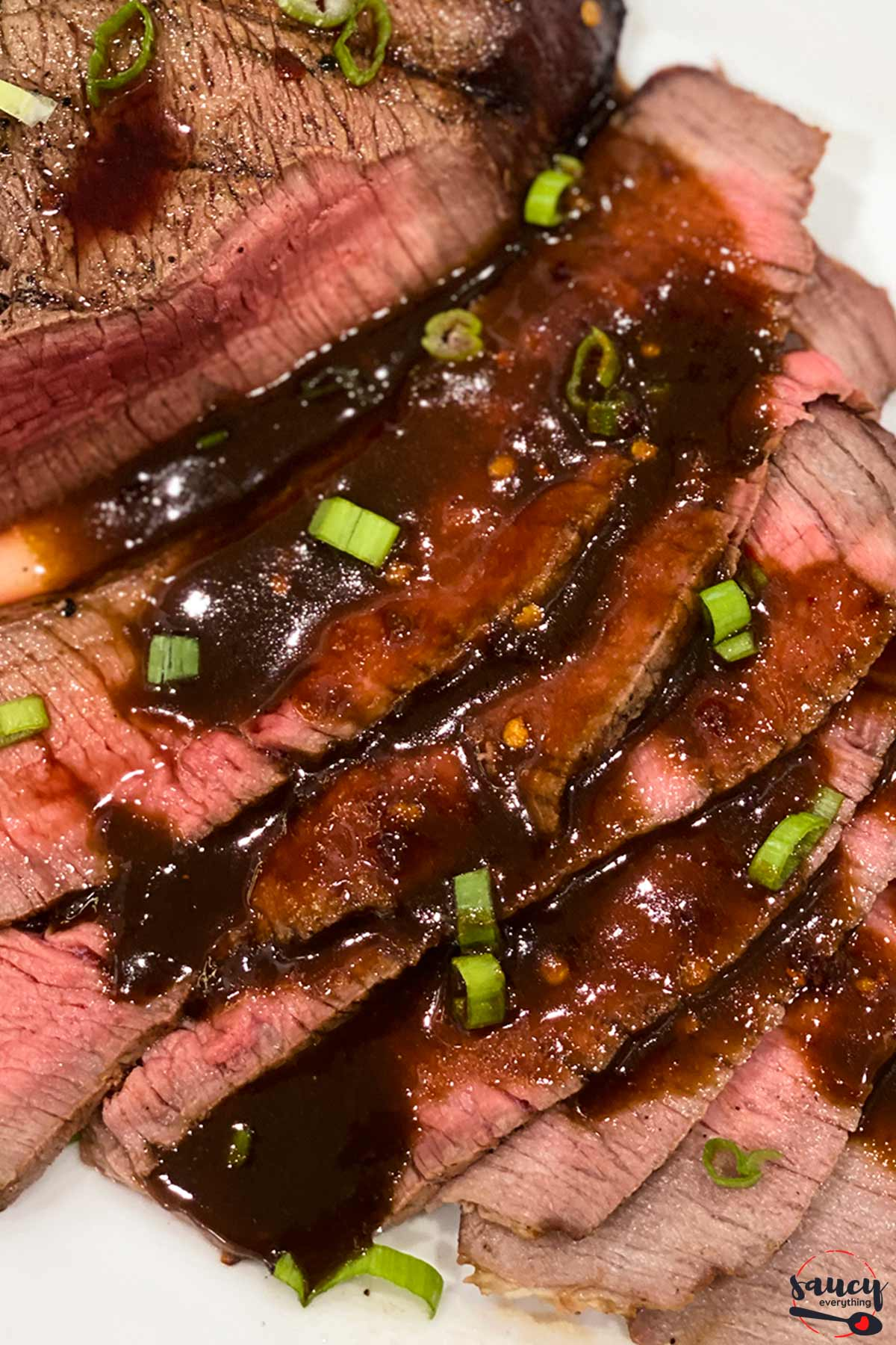 Slices of grilled london broil with sauce
