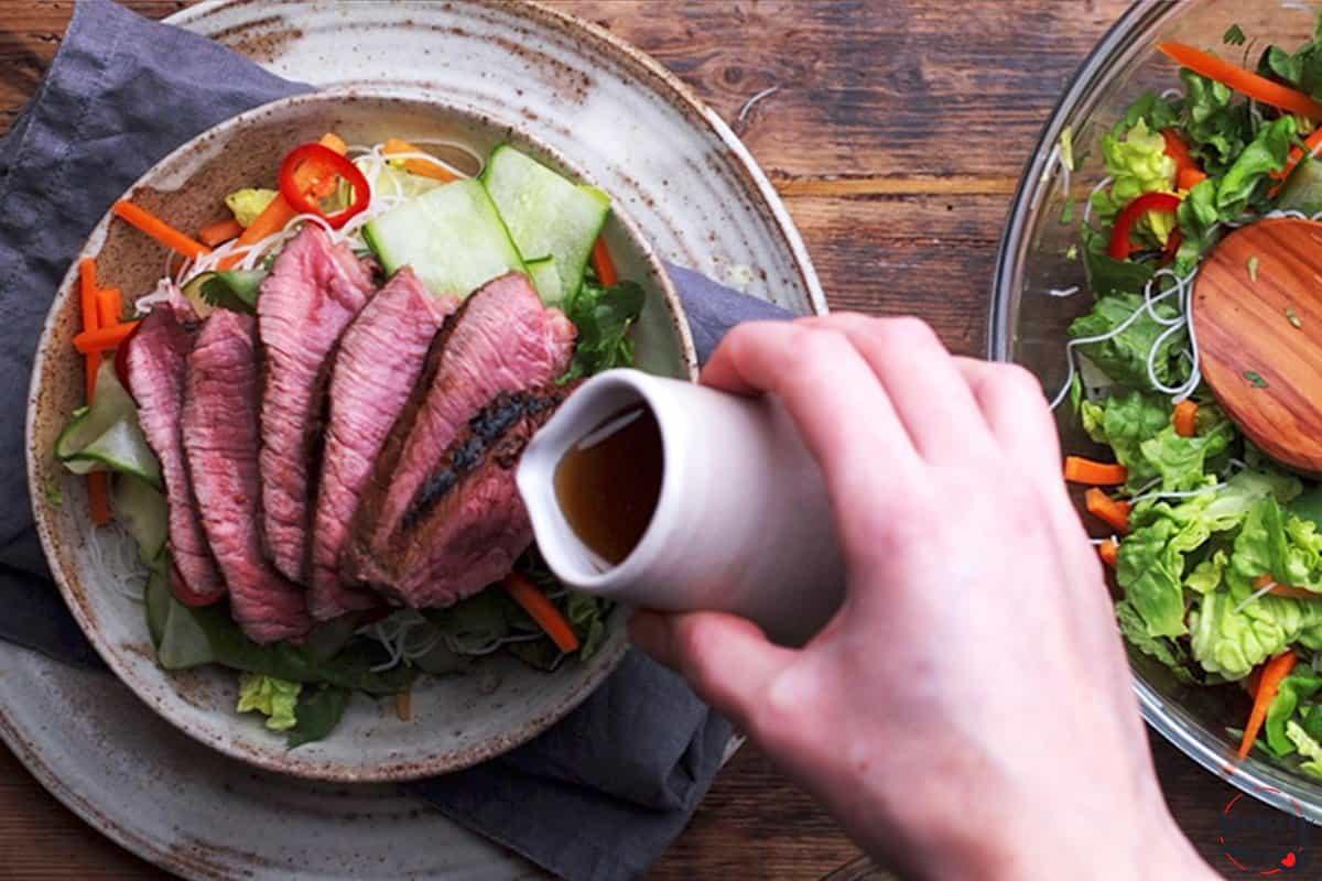 Pouring vietnamese salad dressing over a steak rice noodle salad