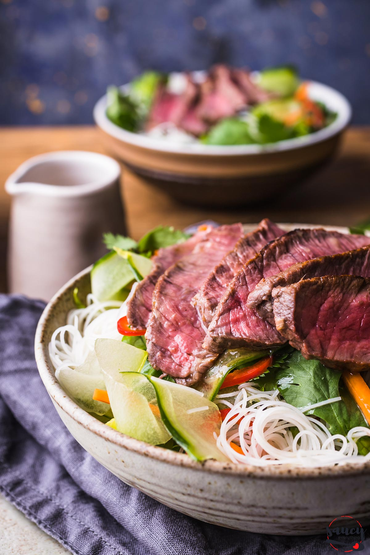 Close up of rice noodle beef salad with dressing in a small pitcher