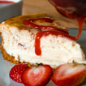 Cheesecake slice on plate with strawberry sauce drizzled on