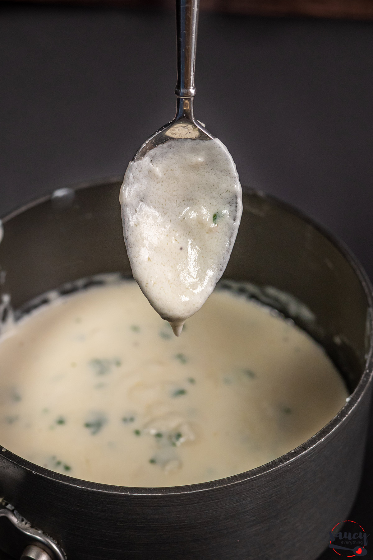 Dripping garlic cream sauce off a spoon