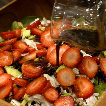 pouring honey balsamic dressing out of a pitcher onto salad