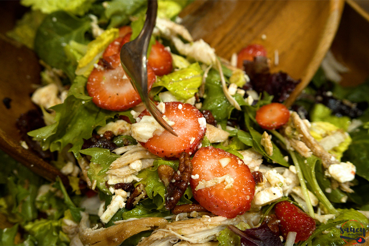 mixing a salad with honey balsamic dressing