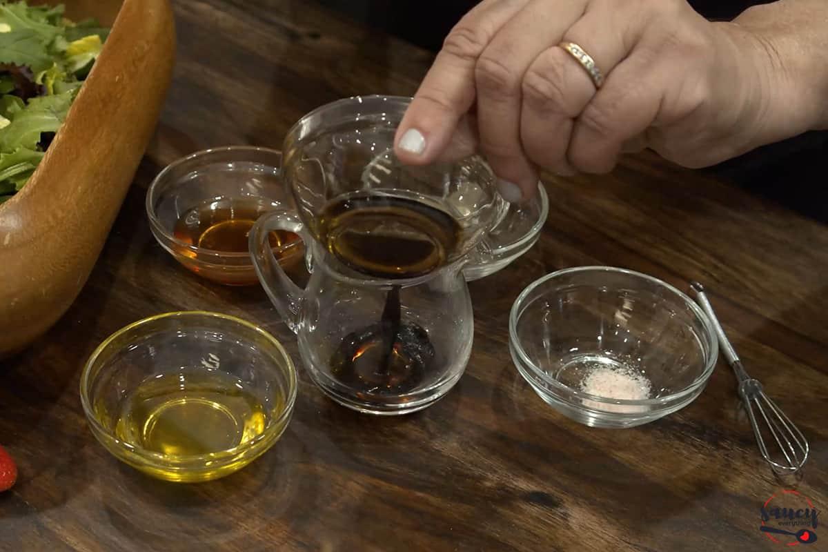 mixing ingredients in a bowl to make honey balsamic vinaigrette