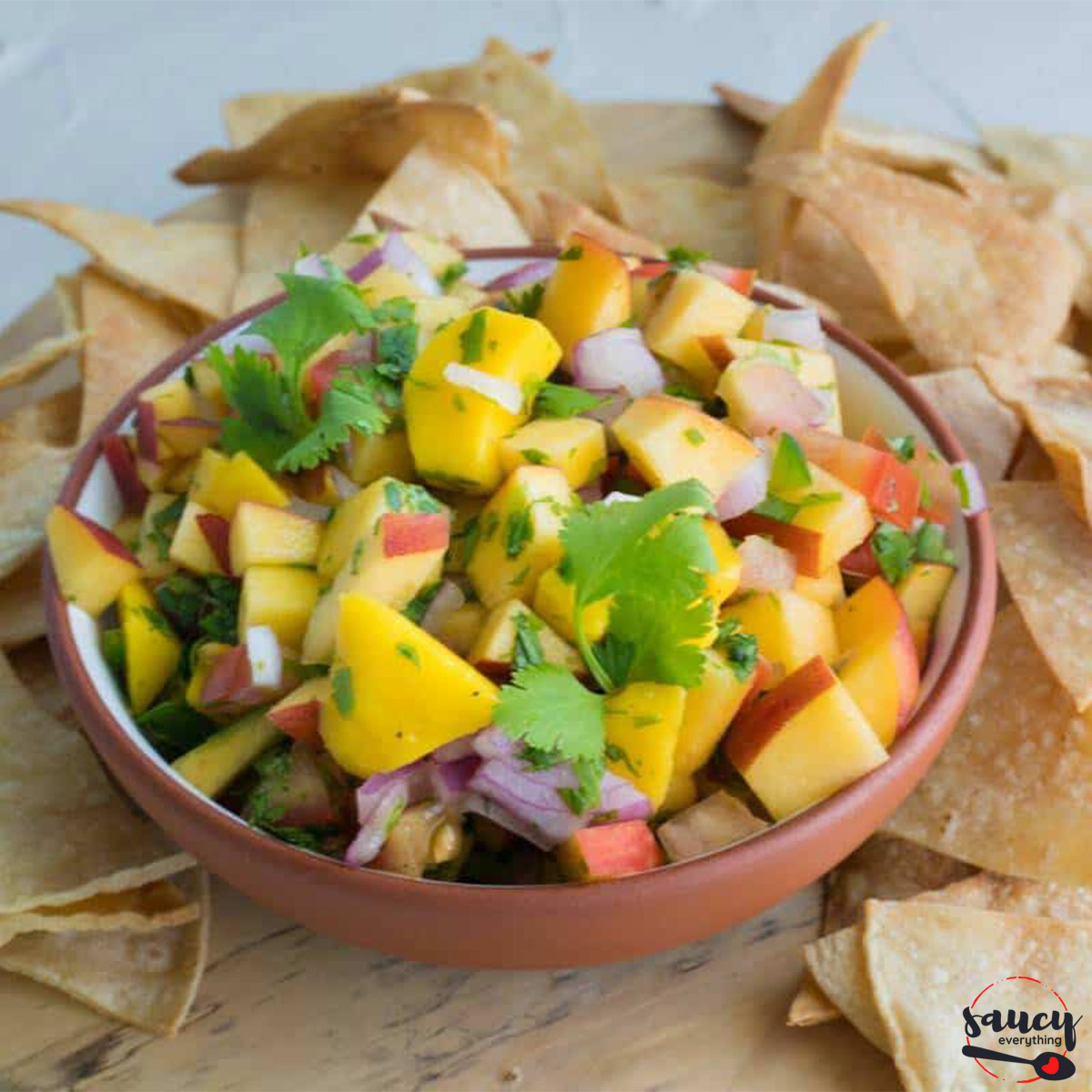 Peach salsa in a bowl next to chips