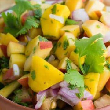 A bowl of peach mango salsa by tortilla chips