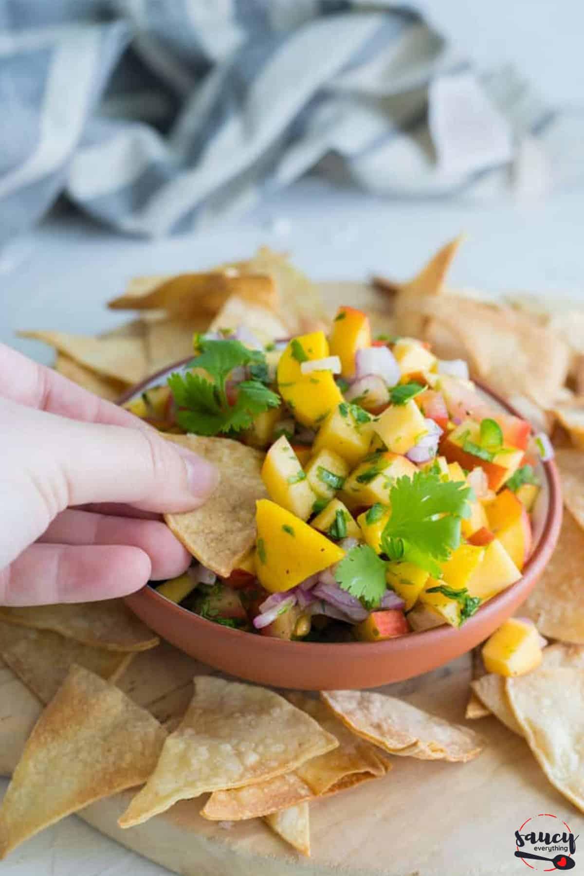 Dipping a chip into peach mango salsa