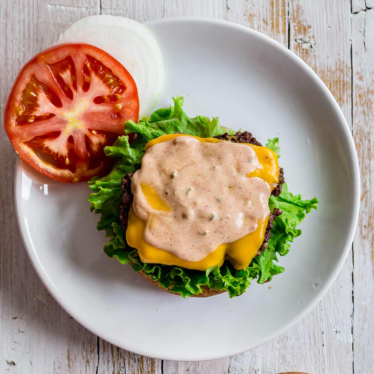 open face burger topped with burger sauce on a plate