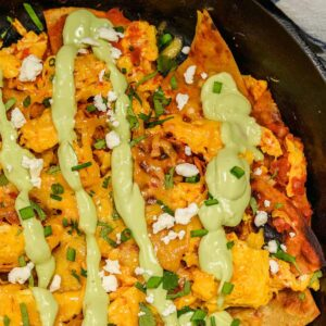 Avocado crema drizzled onto chilaquiles in a skillet