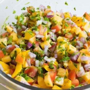 Mixing peach mango salsa in a bowl