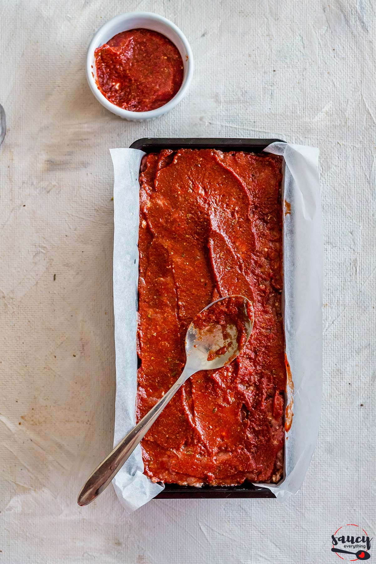 Spreading meatloaf glaze on meatloaf with a spoon