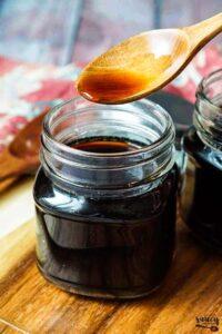 holding a wooden spoon over a jar of teriyaki sauce