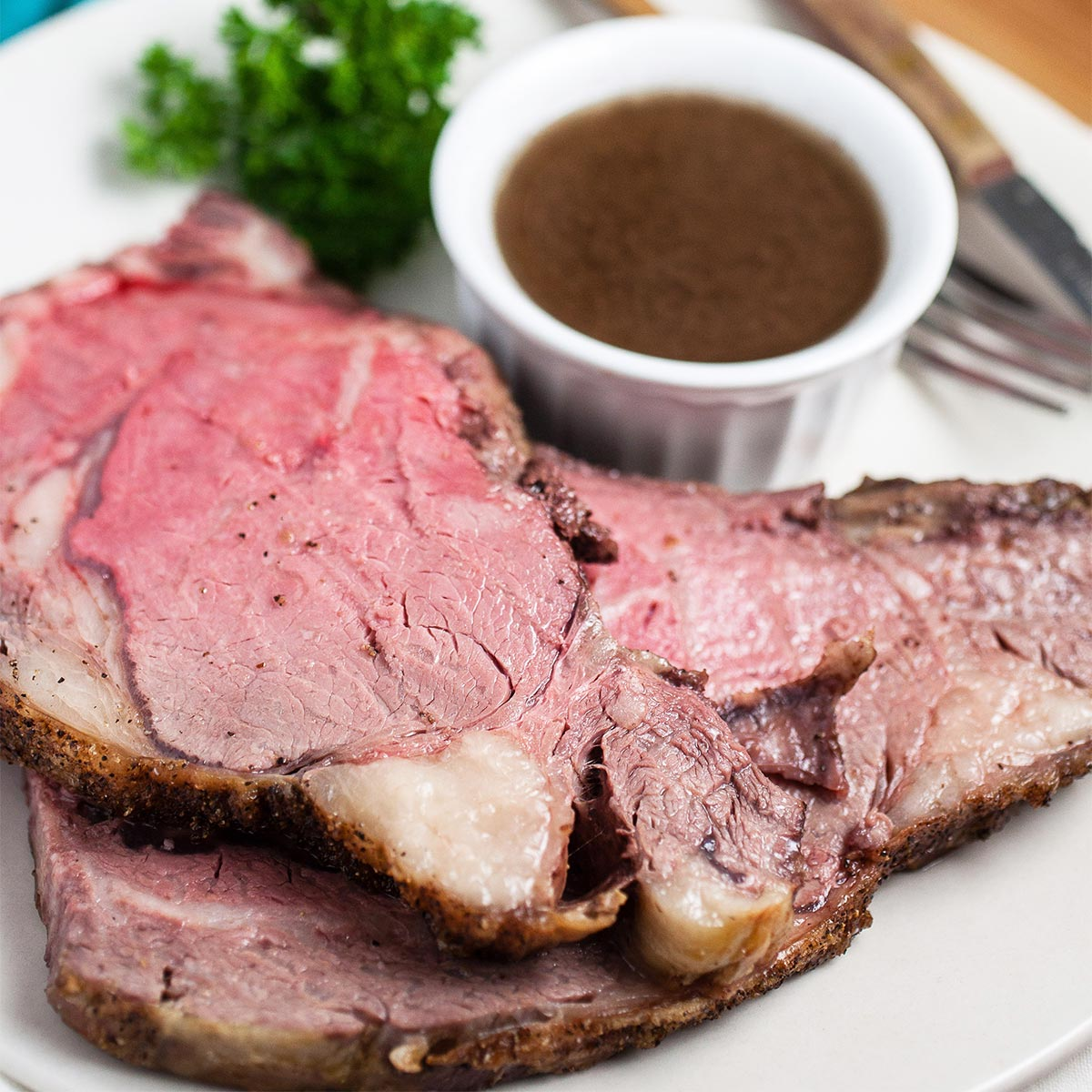 au jus sauce in a bowl next to two slices of prime rib