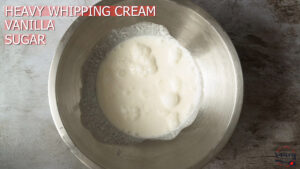Ingredients for whipped cream in metal mixer bowl