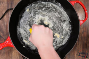 Squeezing lemon juice into a skillet of butter