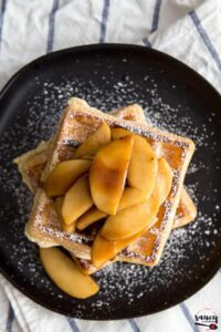Sauteed apples on waffles with powdered sugar