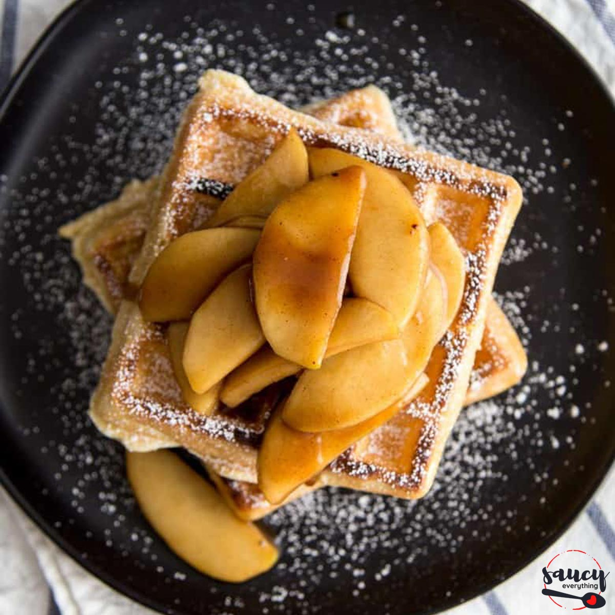 Sauteed apples on waffles with powdered sugar, on a black plate